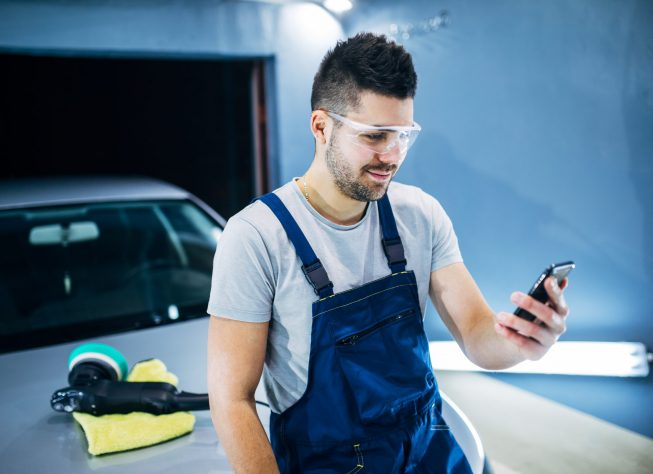 Man holding the phone while doing car polish in his workshop.
